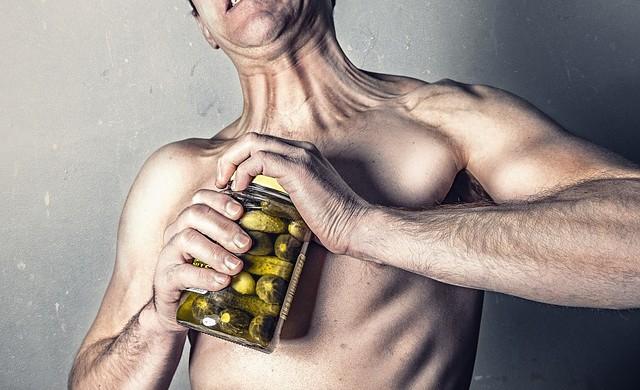 foto de un hombre intentando abrir un tarro de pepinillos.