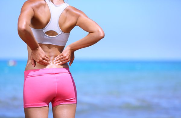 Una mujer en la playa se queja de dolor de espalda